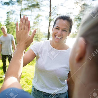 87923302-women-giving-high-five-while-friends-standing-at22-forest