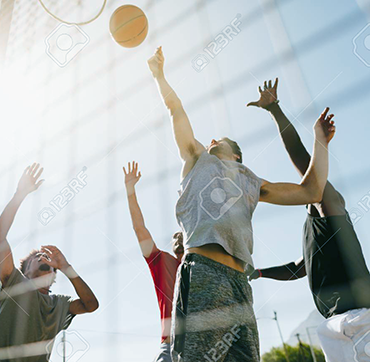 100421952-four-men-playing-basketball-in-a-basketball-court-on-a-sunny-day-men-jumping-hig354h-to-reach-for-the-b